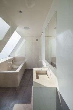 This en suite bathroom features a limestone bath and a skylight with adjustable opacity.