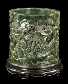 """Chinese Spinach Jade Brush Pot Round spinach green jade brush pot, China, carved with figures in a horse and cart in a landscape scene, on a zitan wood stand, 6"""" x 5 3/4""""."""