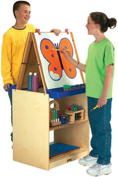 Save space with the Jonti-Craft 2 Station School Age Easel. The twin sided easel is scaled up for the older artist. The removable tabletop hardboard easel Easels For Sale, Chalkboard Easel, Wood Display Stand, Preschool Furniture, Nursery Furniture Sets, Art Easel, Wooden Easel, Modern Kids, Kids Rugs