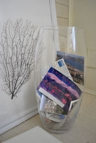 Postcards in a large clear vase... simple accent decor for guest bedroom or powder room