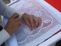 Rendeira labirinteira executando uma peça. Renda crivo ou labirinto é uma renda bordada na qual os desenhos são obtidos através de um tecido no qual é retirado uma quantidade de fios, formando uma grade, que então é preenchida para formar estes desenhos.