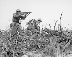 Marine from the 2nd Battalion, 1st Marines on Wana Ridge provides covering fire with his Thompson submachine gun, May, 1945