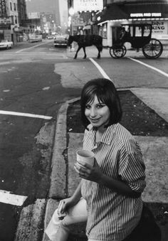 Streisand's Snack. Slim Aarons.  American singer and actress Barbra Streisand partakes of a sandwich and a hot drink in a Chicago street, circa 1970.