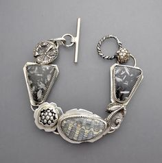 A natural and earthy themed sterling silver bracelet with a beautiful fossil clam shell cabochon at the center with two natural black writing stone pieces. Bold silver elements also. Seven inches in length.