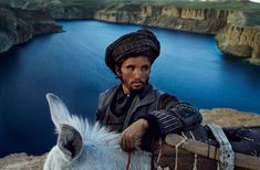 Steve McCurry AFGHANISTAN, Bamiyan Valley, 2006. A man and his donkey on top of a cliff.