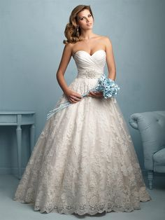 Allure Bridals 9202   For the bride who wants everything — this strapless ballgown features a pleated bodice and crystal detailing, along with a lace applique overlay.