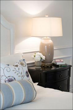The dark wood bedside tables add contrast to the space