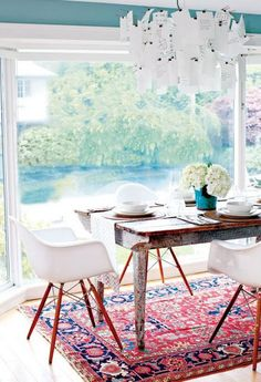 Love this eclectic dining room- the Eames chairs, rustic dining table and traditional rug are perfect together