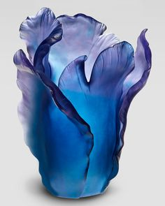 "Daum	 Blue ""Tulip"" Vase Crafted in the shape of a blooming tulip, this exquisite vase makes an engaging vessel for holding a bouquet of fresh flowers. Or simply display it as an elegant objet d'art.       Handcrafted of lead crystal."