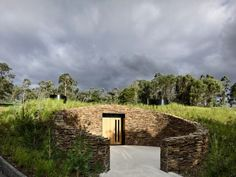 A doorway discreetly set into a circular stone wall leads into this moody subterranean wine cellar that architect Kerstin Thompson has created at Australia's TarraWarra vineyard.