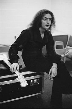 Ritchie Blackmore from rock group Rainbow posed sitting on a flight case…