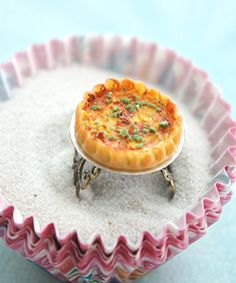 this ring features a miniature handmade cheese quiche. it measures about an inch in diameter and is securely attached to a bronze filigree ring that fits most ring sizes.