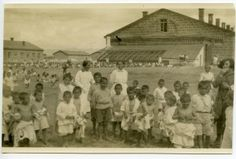 Group of young boys in white uniforms and shorts with two female relief workers in the yard at Alexandropol.