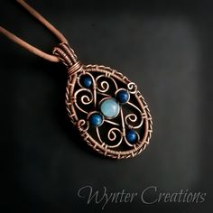 Feminine and classic, this Victorian-inspired pendant features graceful copper filigree embellished with soft blue gemstones.