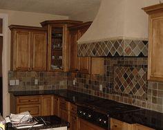 slate backsplash with dark granite and light cabinets