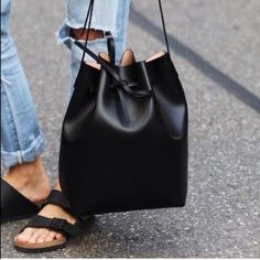 """(2 LEFT!) Le Bucket Tote No trades!! Price is firm!! Fully black interior/exterior. Vegan leather. Adjustable strap. Comes with a dust bag to keep in for care. It ALSO comes with a matching pouch bag on the inside. Find me on instagram: @theanalyssa (these bags are being sold at my clothing store so it is first come first serve). Medium open tote bucket Drawstring closure About 9 x 11 x 3 inches Adjustable strap at 48"""" long Revolt Society Bags Satchels"""