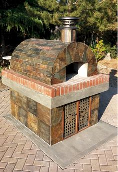 This beautiful wood-fired pizza oven was built with the Cortile Barile foam pizza oven kit. What makes this oven special is the amazing tilework with colorful slate tile and matching base.  BrickWoodOvens.com