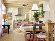 If your space is two rooms in one, make sure they are connected by decor, color and style. Here, there is no break between the living area and the small dining area. The colors, materials and modern eclectic style are carried through this open space, but each small section is focused and defined by area rugs and furniture placement.