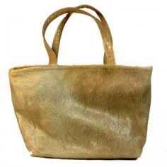 """Gold dyed Hair on Cowhide tote with gold leather handles. Interior with 3"""" leather top and beautiful crushed velvet lining. One leather zippered interior pocket and 2 open hand beaded, fabric pockets. Leather strap with brass toggle for easy to find keys. Magnetic closure. 18""""wide x 12"""" high with 5"""" soft bottom."""