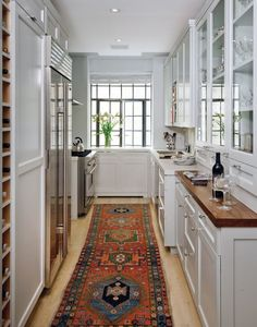 Galley kitchen with runner // small kitchen, glass cabinets, wine storage
