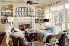 Inspired by the locale, this living room incorporates shades of blue, cream, and gray throughout. Buttery-colored paint highlights the architectural details, from the coffered ceiling to the redded mantel. Patterned wallpaper that's been carefully applied to the backs of two built-in bookcases adds custom style.