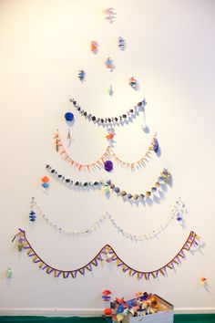 "No space for a tree? Simply hang ornaments and garland on a wall to create a modern ""wall"" tree."
