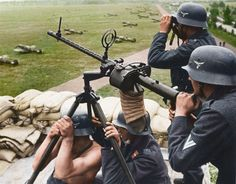 A Luftwaffe anti-aircraft team operating an MG-15 7.92 mm machine gun at an airfield perimeter in the summer of 1939. Note the attached canvas spent shell catcher and Messerschmitt Bf 109s in the background.