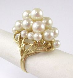 PEARL AND FOURTEEN KARAT GOLD RING, set with a cluster of 18 round white pearls with diameters ranging from 4.4 to 6.9 mm. Ring size: 7-3/4. Estimated to sell between $300-400. To be sold as lot 0514-0389.