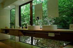 """Embrun House"": Windows above and below the master vanity open the bathroom up to the surrounding forest. A narrow ribbon of wall behind the cabinets carries the plumbing, completing the illusion that the sink area is floating. 