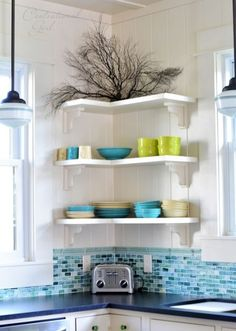Floating shelves are super adaptable and can fit anywhere — even in an inconvenient corner between two windows. Placing bulky cabinets in this space would have eaten up the storage potential – and now the prettiest bowls and plates add to the room's decor. Click for more easy kitchen storage.