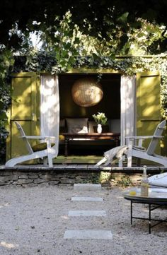 Gorgeous olive colored ivy covered small cabin with deck and lush interior with coffee table
