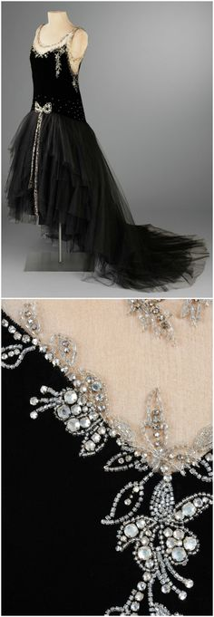 Evening Dress, by Bergdorf Goodman, New York, 1929, Hillwood Estate, Museum & Gardens. Sleeveless evening gown with dropped waistline. Bodice is black silk charmeuse with flesh colored double faced silk organza at neck and sleeve, giving the illusion of a nude shoulder. Bodice is encrusted with punched rhinestones. The skirt consists of asymmetrically cut tulle layers with a decorative rhinestone bow applied flat at center front waist with two free hanging beaded ties.