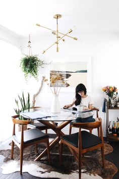 At Home with New Darlings // Wood table and chairs // snake plant // gold light fixture // dark floors light walls