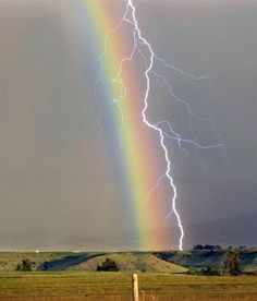 A lightning bolt strikes through a rainbow during a thunderstorm