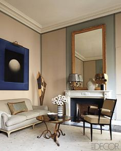 The sofa, chair, and Gilbert Poillerat lamp in the master bedroom designed by Jean-Louis Deniot are circa 1940, the cocktail table is by René Drouet, and the artwork is by Marco Tirelli; the mirror and Carrara-marble mantel are Louis XVI, and the sculpture in the corner is by Emile Gilioli.