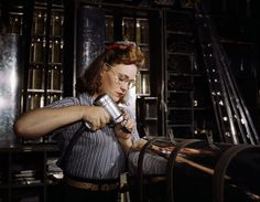 Operating a hand drill at the North American Aviation, Inc., [a] woman is in the control surface department assembling a section of the leading edge for the horizontal stabilizer of a plane by Alfred Palmer - 1942