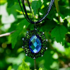 This stunning sapphire crystal necklace is made with black metal filigree, tiny sparkling vintage rhinestones, and comes pre-hung with black ribbon and cord. The pendant measures approximately 2 inches long by 1.5 inches across. The ribbon is 18 long and, when fastened around your neck, this necklace hangs about 9 down, hitting about mid to upper-chest.  My Sapphire Blue Gothic Crystal Necklace will make an excellent addition to your collection of Gothic, Bohemian, Woodland, or…