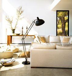 Moderna a luminária de chão direciona a  luz  sobre o sofá. Ideal par leitura ou trabalhos manuais.