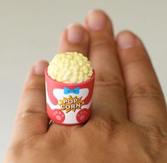 A super cute Bucket of Popcorn!!! Perfect Snack!!! It measures approx. 0.75 inch wide and 1.25 inch high is on a silver plated adjustable bang that will fit most ring sizes.