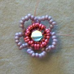 Flower 17. Repeat adding petals of 7xA beads around the bezel.  Step up at the end of the round by going up through the first bead of the first petal.