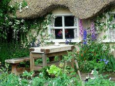 cottage garten strohdach sommerblumen sitzecke