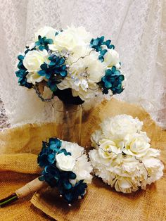 Ivory grand peonies, cream roses, teal hydrangea clusters make up these bouquets for bride, bridesmaid and toss.  Rustic silver beaded wire cross over the top and burlap accents the stems.  The bridal bouquet has a family heirloom rosary woven within the blossoms.