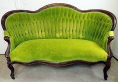 Victorian settee with a curvaceous wood frame in an intensely grained wood, upholstered in avocado green velvet. The shaped tight back is vertically tufted with three rows of buttons with a smooth seat and pads at the arms.