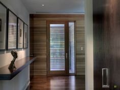 a charming wooden door with thin glass window for modern house with wooden flooring and wooden floating shelf with artistic and classic decors