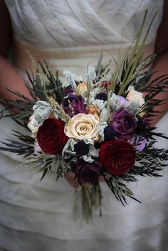 Consists of dried and preserved burgundy garden roses, dried and preserved cream roses, dried and preserved lilac roses, handmade deep plum paper roses, and dried and preserved foliage and filler. Wrapped in a gold ribbon.