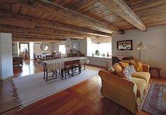 Muhkeat kattoparrut puhaltavat vanhaa henkeä olohuoneeseen. Koko navetan alakerta on yhtä avaraa tilaa.