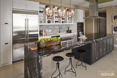 A timeless look for the kitchen with onyx tiles, quartz counters and Brazilian granite for the island. (Kohler)