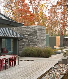 The dining table, a custom design by Formwork, and red Non chairs by Komplot complement the addition's cypress cladding.   Photo by Eli M...