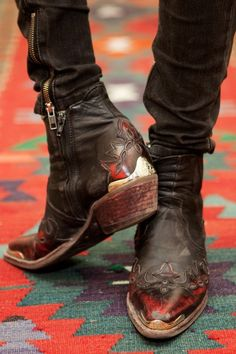 Black leather ankle boots with red detail on toe and heel, after the style of cowboy boots