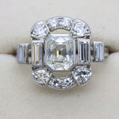 Unusual diamond dress ring, made in France circa 1925. Set on platinum, there is a bright cushion cut centre diamond, and bageutte sides with a surround of pavé set diamonds. A really beautiful piece.
